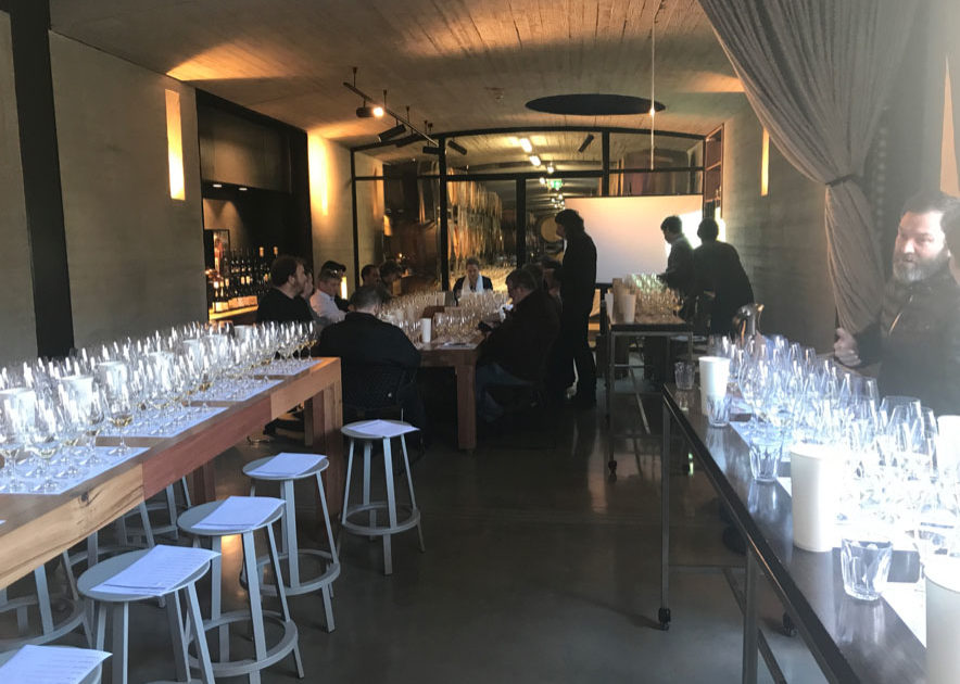 Wine Week in Restaurant: minimalist, modern white decor with about six pwoplw in the background