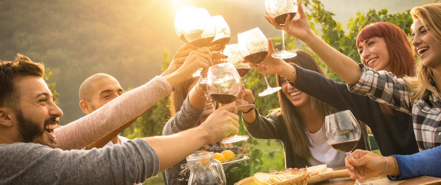 A group of friends sitting around a table cheers-ing with a glass of red wine with share plates on table