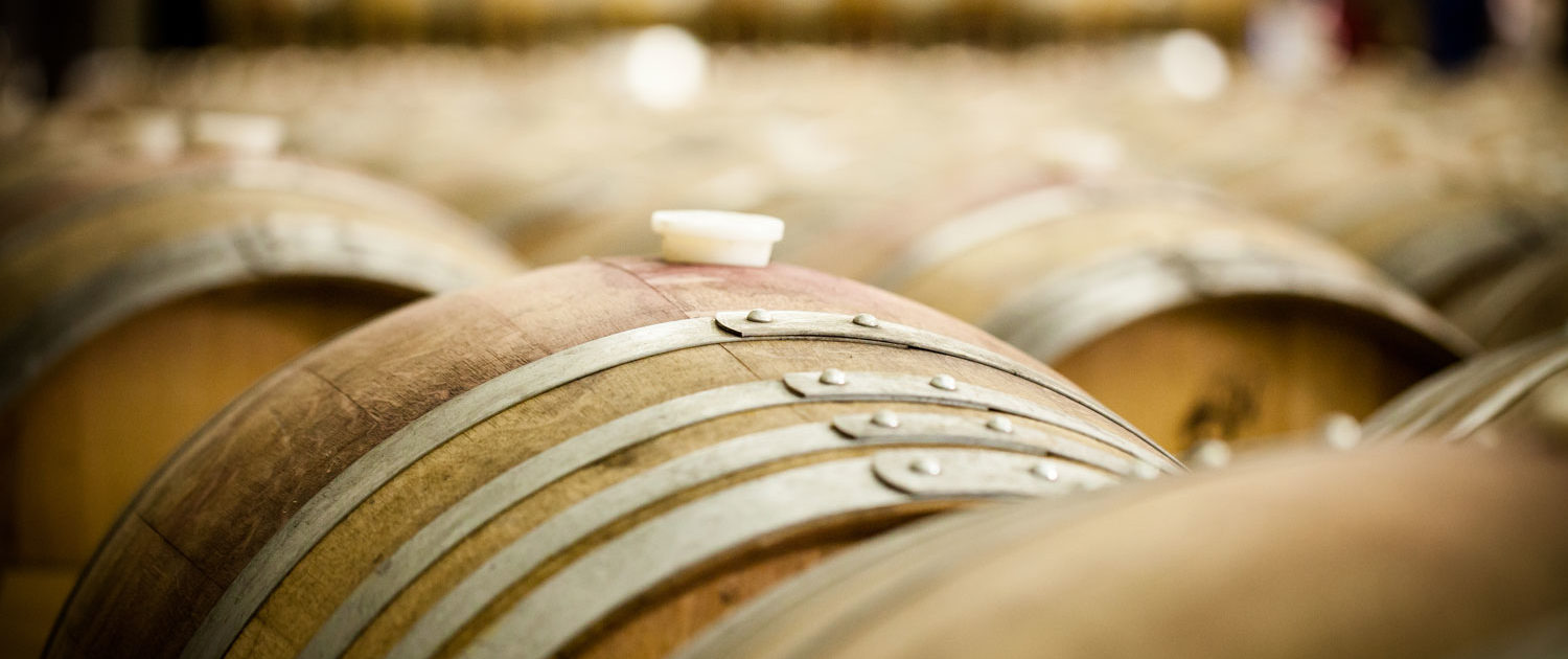 Photo of wine barrels in barrel hall, focus is of one barrel, with other barrel's out of focus