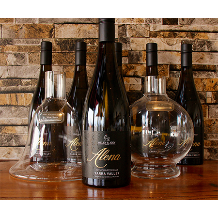 Six bottles of Alena Chardonnay along with two glass decanter trophies sitting on a polished wooden table infront of ornate brick wall